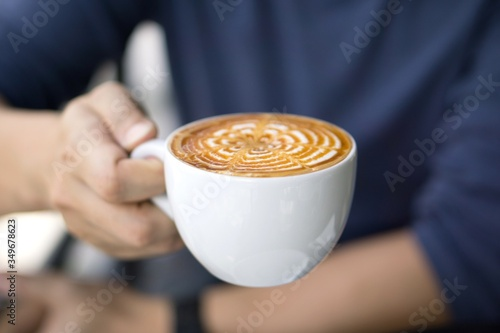 Midsection Of Man Holding Froth Art On Coffee In Cup Poster Mural XXL