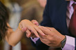 Close-up Of Bridegroom Inserting Wedding Ring In Bride Finger