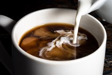 Close-up Of Milk Being Poured In Coffee