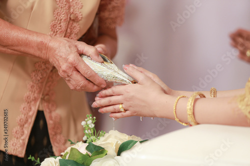 Foto Midsection Of Woman Performing Rituals With Bride And Groom During Wedding