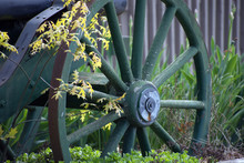 A Wagon Wheel With Yellow Leaves In Front.