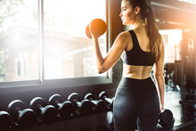 Rear View Of Young Woman Exercising With Dumbbells In Gym
