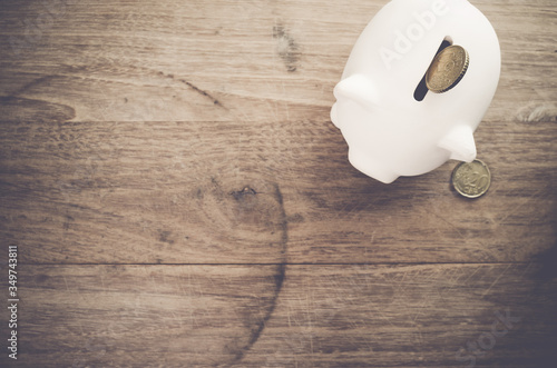 Fotografia Directly Above Shot Of Piggy Bank And Coins On Wooden Table