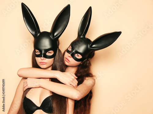 Two sexy beautiful women wearing carnival black mask of Easter bunny rabbit Canvas Print