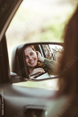 Fotografia, Obraz reflection on stunning smiling woman in car rear mirror