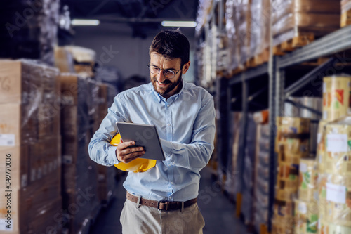 Fototapeta Young handsome bearded employee holding protective helmet under armpit and using tablet to check out goods. obraz