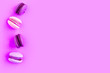 canvas print picture - Pink sweet macaroons on purple background. Top view, minimal concept, copy space for the text
