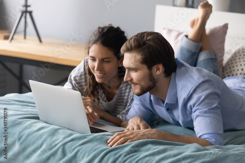 Fototapeta Happy young man and woman relax lying in cozy bed browsing fast wireless internet shopping on laptop together, millennial Caucasian couple rest in bedroom watch video using modern computer at home obraz