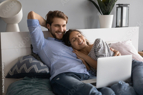 Photographie Happy young Caucasian couple lying relaxing in comfortable bed watching video on