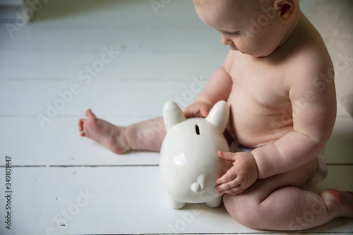 Fototapeta A baby holding onto a piggy bank. cost of raising a child concept obraz