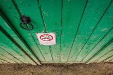 Heavily Flaking Green Paint Seen On A Shut Wooden Door At A Stables. A No Smoking Sign Has Recently Been Added To The Door, Warning Stable Users Of The Law.