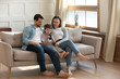 Happy young Caucasian family with son sit relax on sofa in living room using modern smartphone gadget together, smiling parents rest on couch at home with small boy child, browsing cellphone device