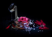Close-up Of Diamonds And Pearls With Artificial Flower Against Black Background