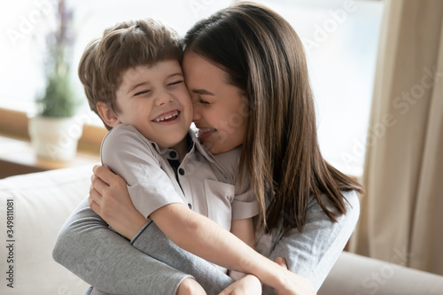 Fototapeta Happy young Caucasian mother hug cuddle cute little preschooler son enjoy tender time together at home, smiling mom embrace small boy child show love and care, bonding, family unity concept obraz