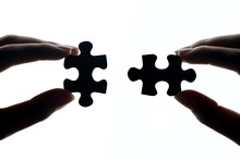 Cropped Hands Of Person Holding Jigsaw Piece Against White Background