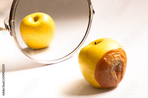 Apple in good condition looking at itself in the mirror while its back is rotten Poster Mural XXL