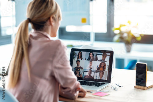 Fotografie, Tablou Female employee speaking on video call with diverse colleagues on online briefing with laptop at home