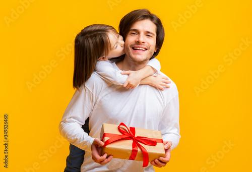 Fototapeta Little daughter kissing birthday father over yellow background obraz