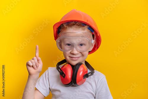 Cute boy in builder glasses, helmet and headphone to ear protection shown finger Wallpaper Mural