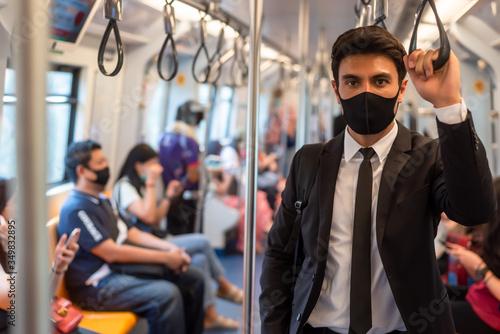 Portrait of confident businessman in black suit wear mask in city finding job du Canvas-taulu