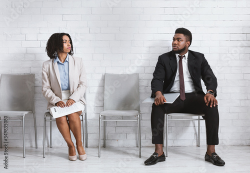 Male and female vacancy candidates looking at each other with antipathy while wa Canvas Print