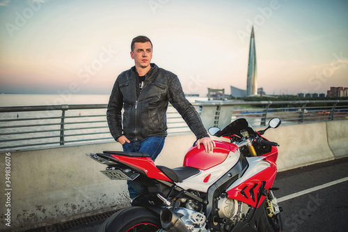 Handsome young man wearing casual outfit standing near red spotts motocycle at r Canvas Print