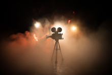 Movie Concept. Miniature Movie Set On Dark Toned Background With Fog And Empty Space. Silhouette Of Vintage Camera On Tripod.
