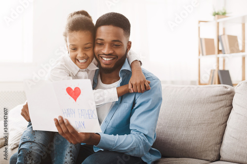 Fotografia Pretty afro girl congratulating dad with father's day