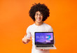 canvas print picture - Funky African American guy pointing at computer screen with blog webpage, orange background. Collage