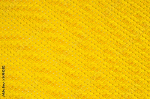 Photo Synthetic yellow perforated stretch fabric, photographed close-up