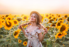 Art Young Village Woman Model Enjoy Summer Nature Sunny Sunset, Stands In Flowering Field. Yellow Orange Flowers Sunflower. Smiling Face Blonde Girl Holding Two Braids In Hands. Rural Boater Straw Hat