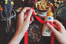 Wiccan Witch Casting Money Spell At Her Altar - Tying Red Ribbon Around Yellow Candle With Money Banknotes Using Her Hands. Slightly Blurred Background With Vintage Golden Jewelry, Flowers On A Table