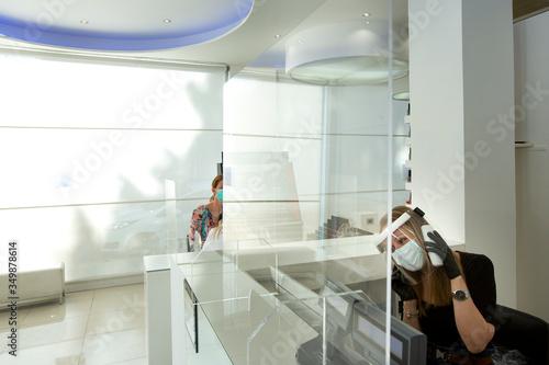 Salone di parrucchieri allestito secondo le regole per la protezione del personale e dei clienti con plexiglass separatori equipaggiamento di personale e clienti Tableau sur Toile