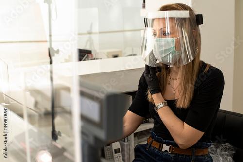 Fotografie, Tablou segretaria di un locale nella postazione di lavoro alle prese con il telefono e