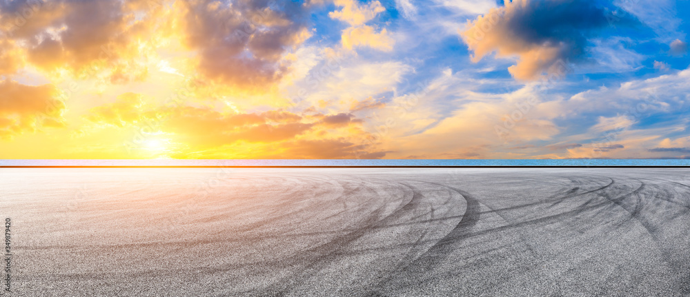 Fototapeta Race track road and lake with sky cloud landscape at sunset.