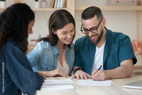Fotografie, Obraz Happy young couple clients make purchase deal sign insurance contract at meeting with estate agent