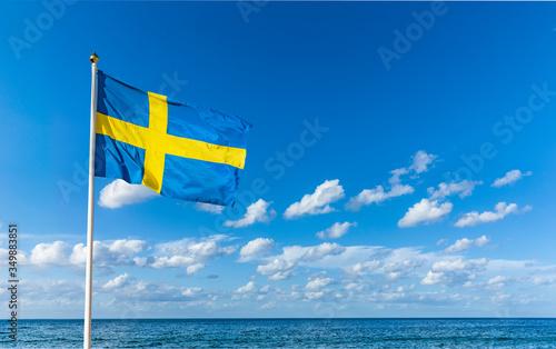 Obraz Schwedische Flagge im Wind vor Blauem Himmel - fototapety do salonu