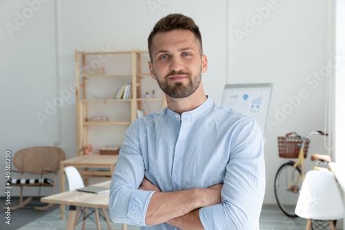Obraz Close up head shot portrait picture of smiling businessman crossing hands looking at camera. Happy confident millennial man manager on workplace background in office. - fototapety do salonu