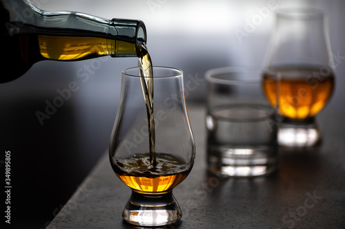Fototapeta Pouring in tulip-shaped tasting glass Scotch single malt or blended whisky obraz