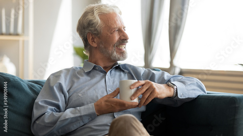 Fototapeta Happy elderly mature grey haired man resting on comfortable sofa with cup of hot tea, enjoying evening morning weekend time at home, smiling old grandfather dreaming of future alone in living room. obraz