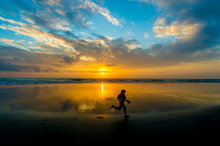 Silhouette Girl Running On Shore At Beach Against Cloudy Sky During Sunset