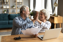 Overjoyed Exited Middle Aged Married Couple Giving High Five, Finishing Doing Domestic Paperwork Together At Home. Euphoric Happy Older Mature Spouses Celebrating Successful Investment Or Purchase.