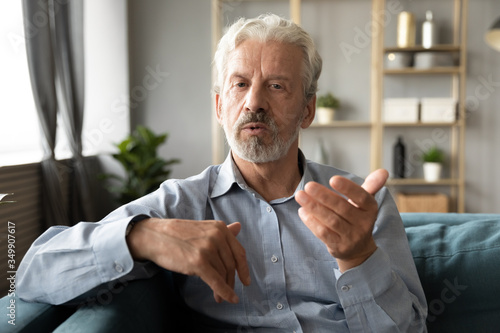 Cuadros en Lienzo Confident hoary middle aged handsome man looking at camera, holding business talk with clients partners online