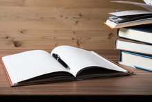 Close-up Of Book And Pen On Wooden Table