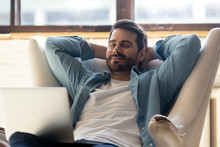 Smiling Young Man Relax In Comfortable Armchair At Home Take Nap Daydream Distracted From Computer Work, Happy Millennial Male Sit Rest In Cozy Chair In Living Room Enjoy Peace, Stress Free Concept