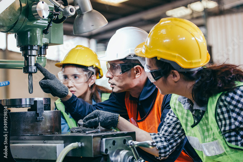 Cuadros en Lienzo Asian male foreman manager showing case study of factory machine to two engineer trainee young woman in protective uniform
