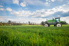 Tractor Spraying Pesticides, Fertilizing On The Vegetable Field With Sprayer At The Spring, Fertilization Concept