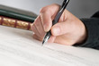 Cropped Hand Of Businessman Signing Contract Paper At Office