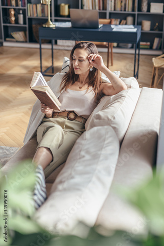 Young woman at home lying on couch and reading book.