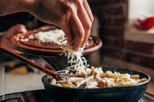 Obraz na płótnie Female hand sprinkles grated cheese on a pan with pasta